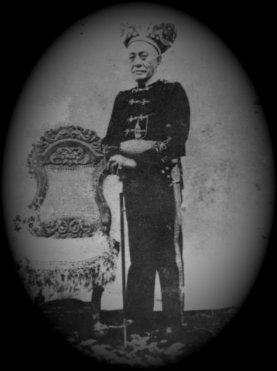 Paduka Raja Hasan van Gobel from Kerajaan Bolaang Uki in clothes of king highness, taking picture beside Kursi Macan
