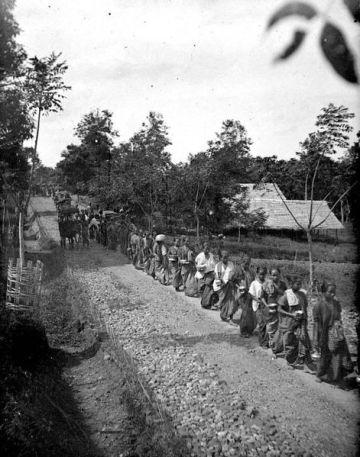 Wanita menunggu di pinggir jalan lewatnya Datu Mario Riawa pada masa Hindia Belanda